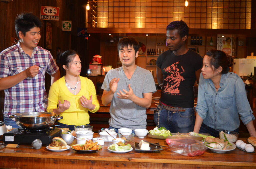 Photo of five people in a restaurant. Promotional image for the documentary Make Food Not War (2020).